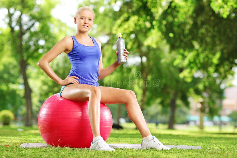 Young female athlete sitting on fitness ball holding a bottle in stock image