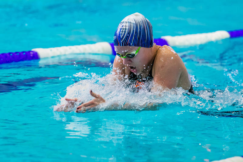 Young female athlete swimming breaststroke in pool royalty free stock images