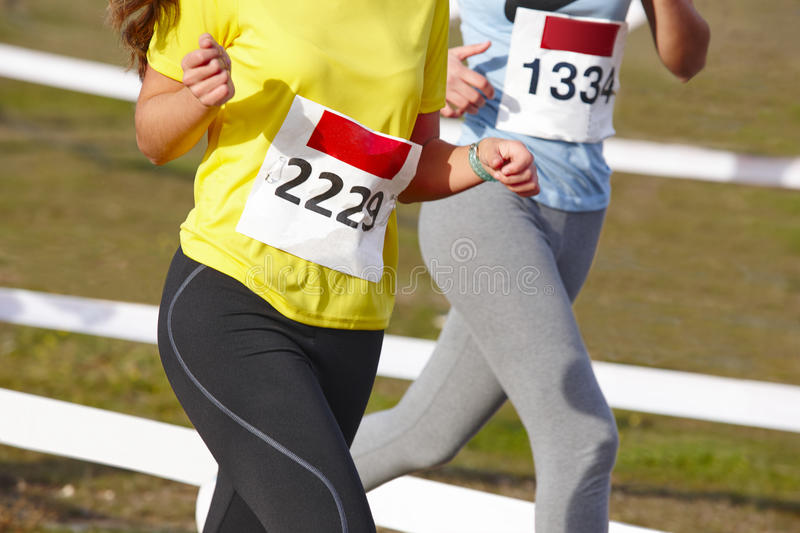 Young female athletic runners on a race. Outdoor circuit. Horizontal royalty free stock images