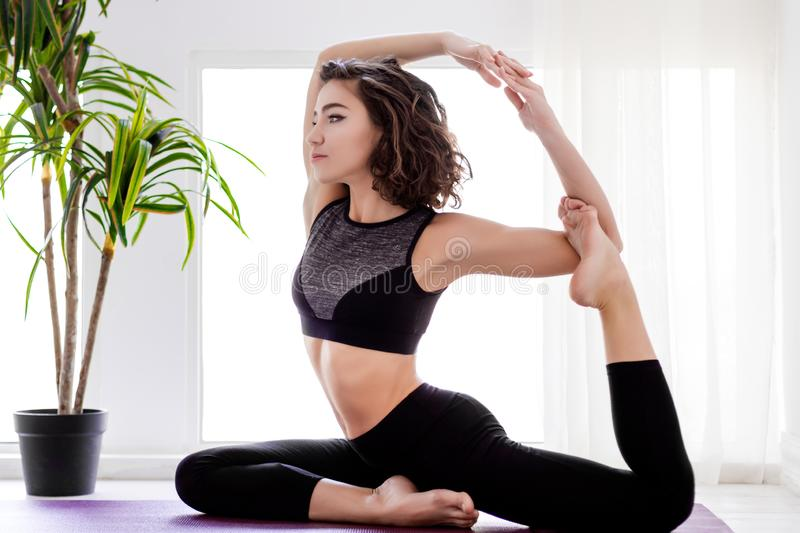 Young woman doing yoga workout at home stock image