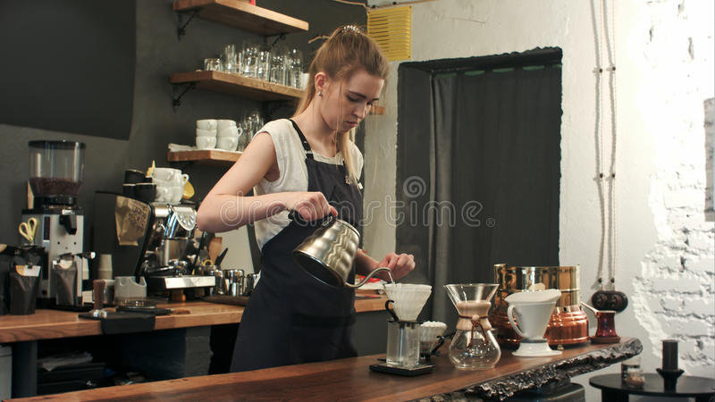 Young female barista in trendy modern cafe coffee shop pours boiling water over coffee grounds making a pour over drip. Coffee. Professional shot in 4K royalty free stock photos