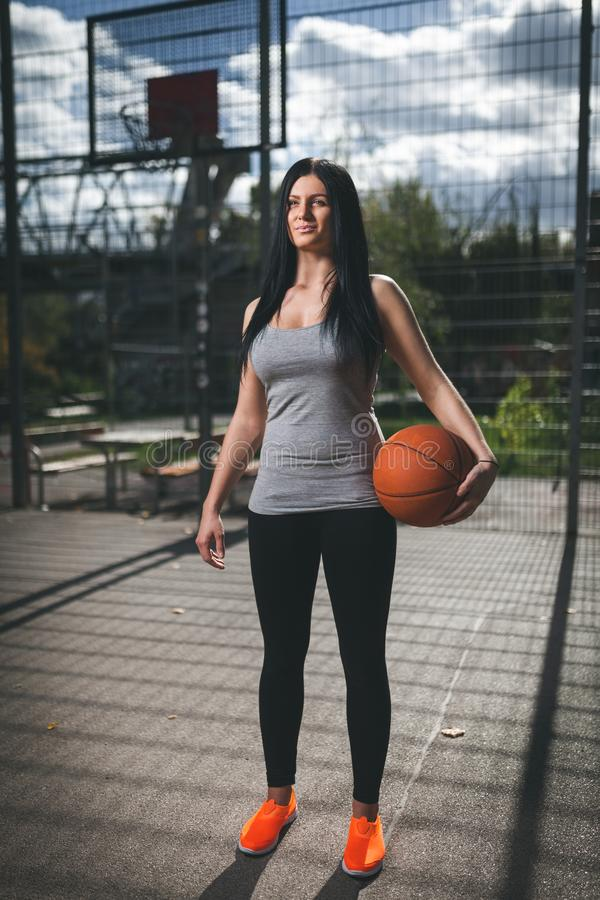 Female basketball player training outdoors on a local court royalty free stock image