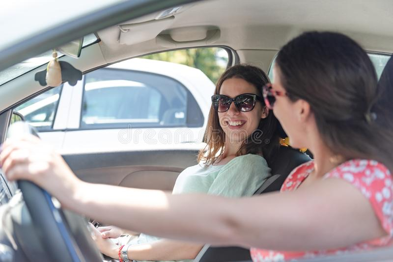 Young female best friends having fun at car roadtrip moment transportation concept and urban ordinary life with women girlfriends royalty free stock photography
