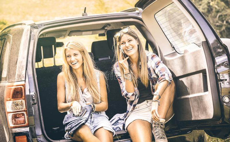 Young female best friends using mobile smart phone and having fun with at car roadtrip moment - Wanderlust concept with women stock photos