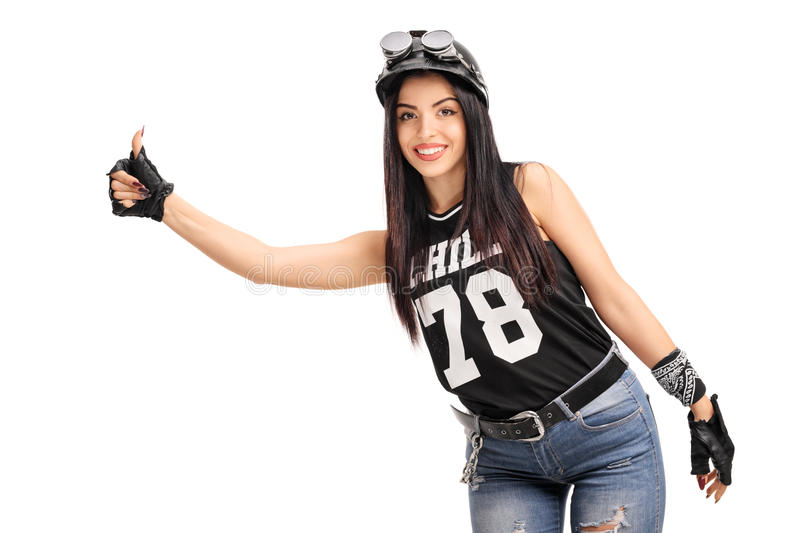 Young female biker hitchhiking with her thumb. Young female biker with helmet and goggles hitchhiking with her thumb on white background stock photography