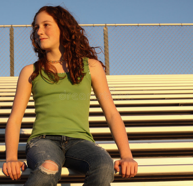 Young female on bleachers. Young teen sitting upon bleachers royalty free stock photography
