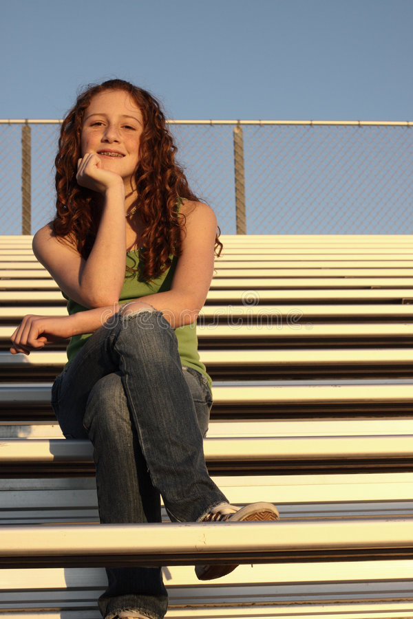 Young female on bleachers. Young teen sitting upon bleachers stock photo