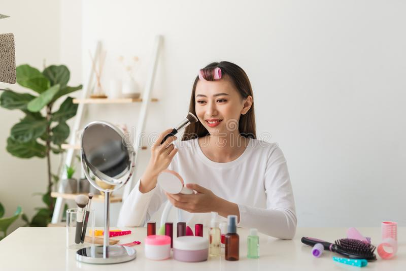Young female blogger with makeup cosmetics recording video at home royalty free stock photo