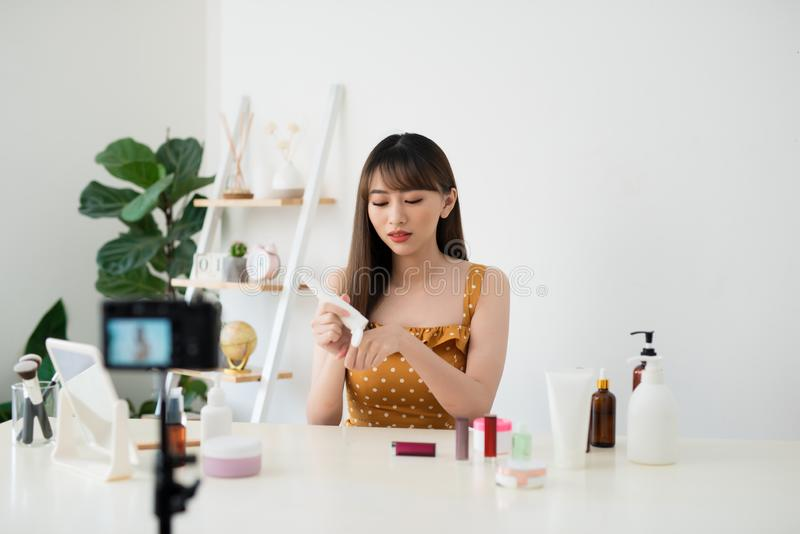 Young female blogger with makeup cosmetics recording video at home royalty free stock photography