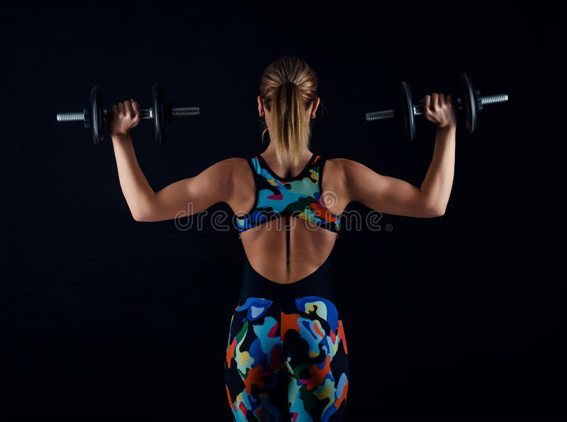 Young female bodybuilder with perfect strong muscular body wearing sportswear tracksuit exercising with weights. Rearview. royalty free stock photography