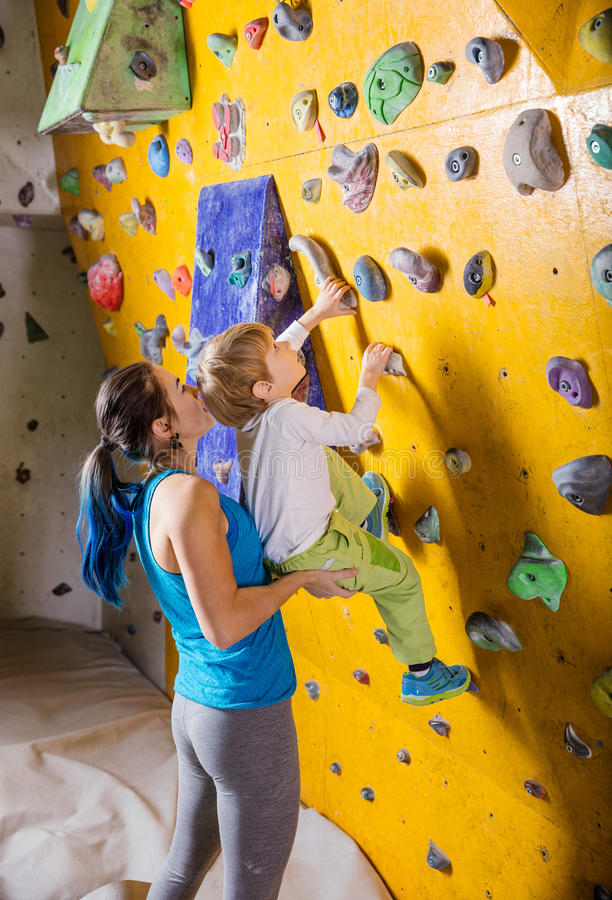 Young female bouldering instructor helping boy climb. Artificial wall stock photo