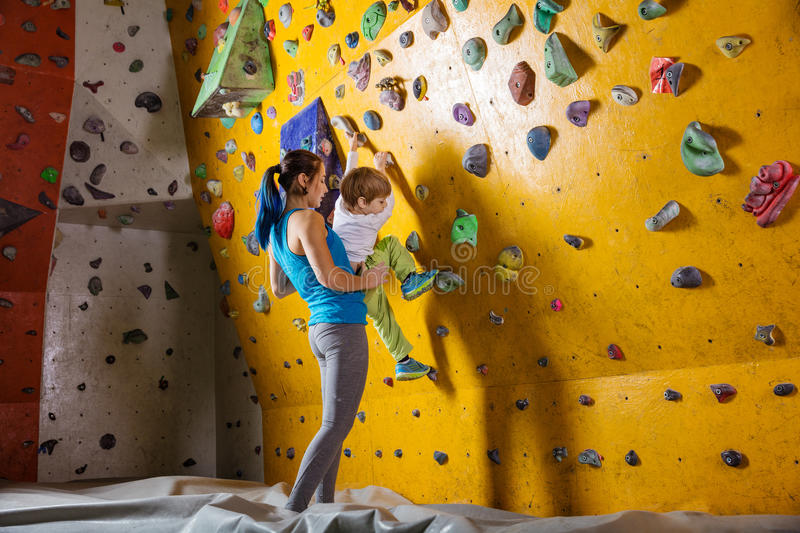 Young female bouldering instructor helping boy climb. Artificial wall stock image