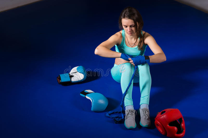 Young female boxer preparing bandages for fight near lying boxing gloves and helmet stock image