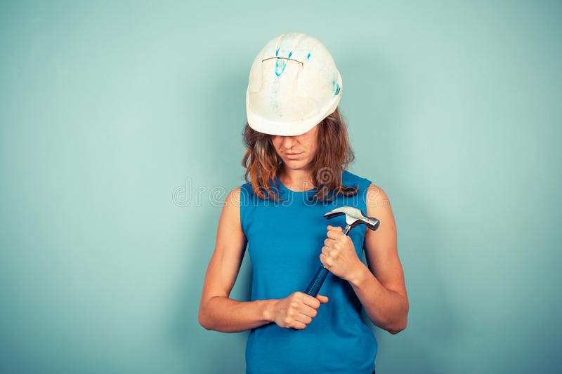 Young female builder with hammer stock image