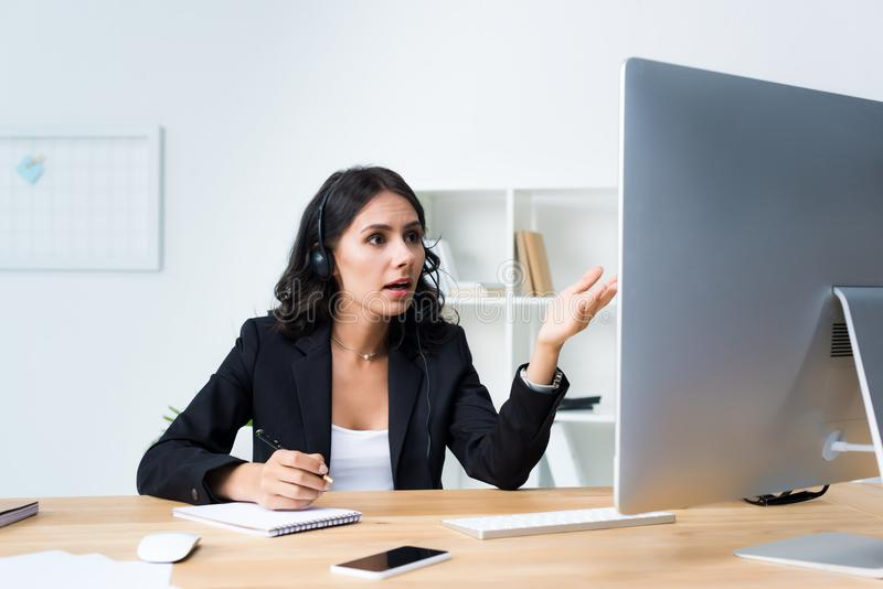 Young female call center worker with headset pointing at computer. While talking royalty free stock photos