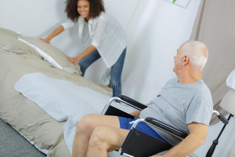 Young female caregiver helping senior man at home stock images