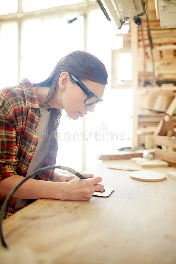 Pyrographic craft. Young female carpenter with pyrographic equipment drawing ornaments on wooden board royalty free stock images