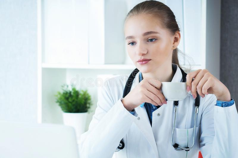 Young female Caucasian doctor having a break and drinking coffee sitting at her workplace. royalty free stock photos