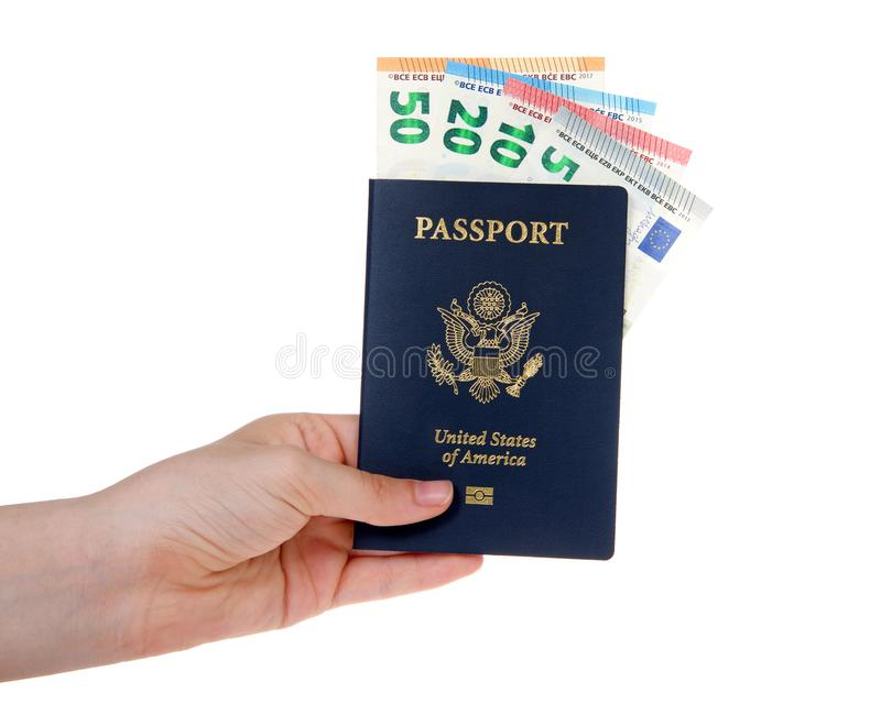 Hand holding American passport with Euro bills sticking out isolated. Young female caucasian hand holding U.S. Passport with European banknotes euros sticking royalty free stock image