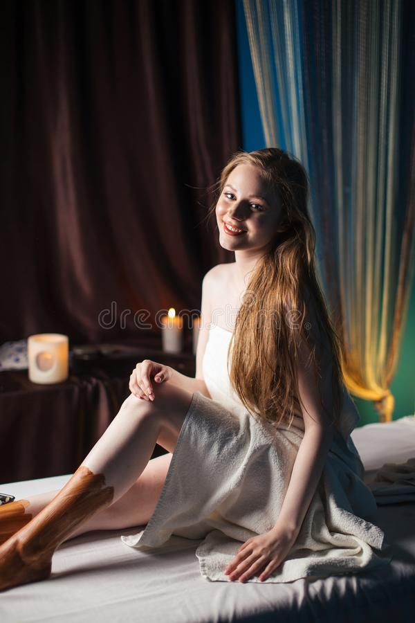 Young female client getting spa treatment in rejuvenation clinic. Mud therapy. stock images