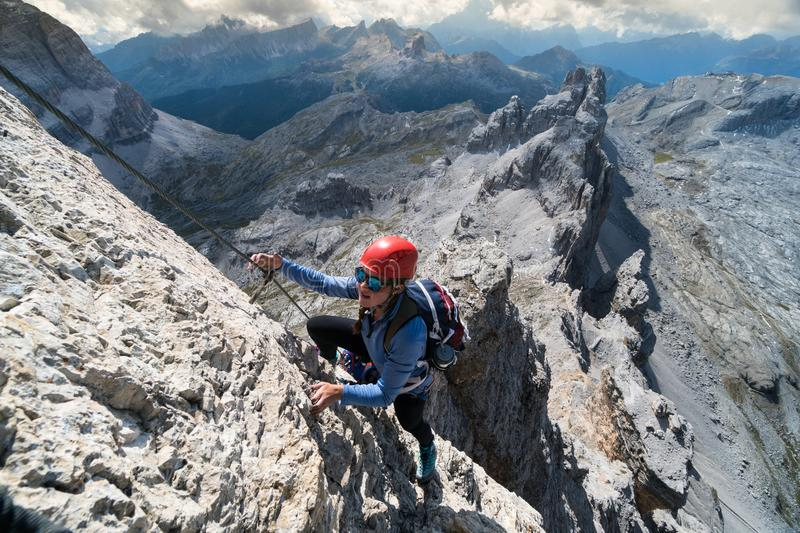 Young female climber on an exposed Via Ferrata in South Tyrol royalty free stock photo
