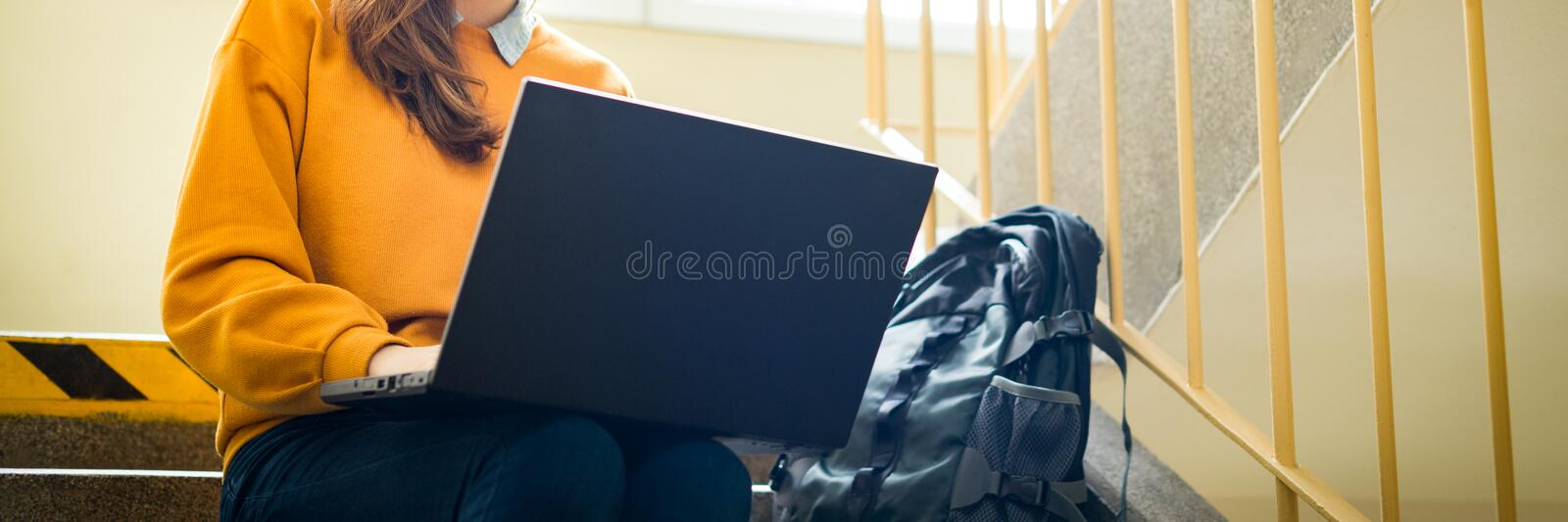 Young female college student sitting on stairs at school, writing essay on her laptop. Education concept. stock image