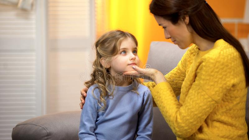 Young female comforting little daughter, touching girls face tenderly, closeness stock images