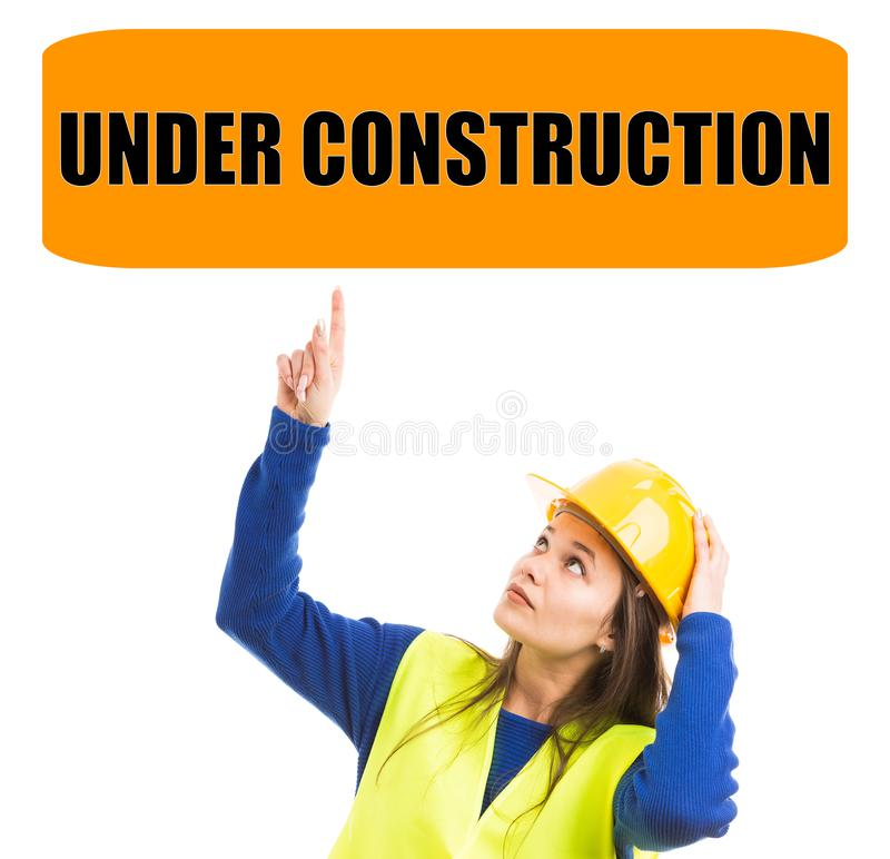 Female construction worker pointing at under construction sign royalty free stock photography