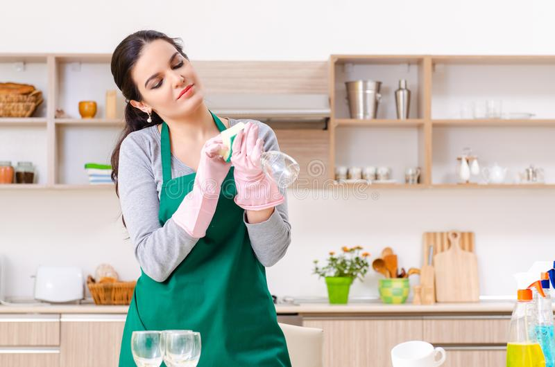Young female contractor doing housework. The young female contractor doing housework stock photography