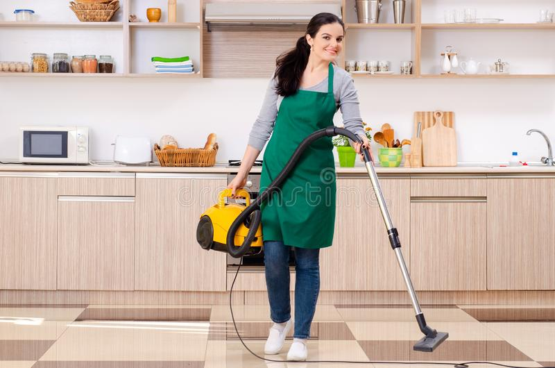 Young female contractor doing housework. The young female contractor doing housework royalty free stock images