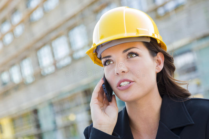 Young Female Contractor Wearing Hard Hat on Site Using Phone stock images
