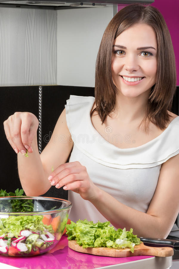 Young female cook making a fresh salad royalty free stock images
