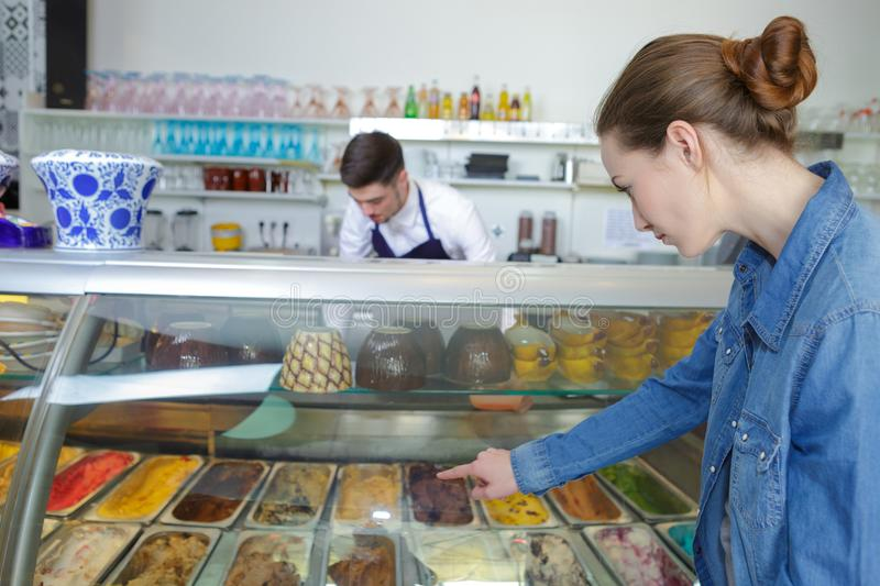 Young female customer choosing ice cream in parlor. Female royalty free stock image