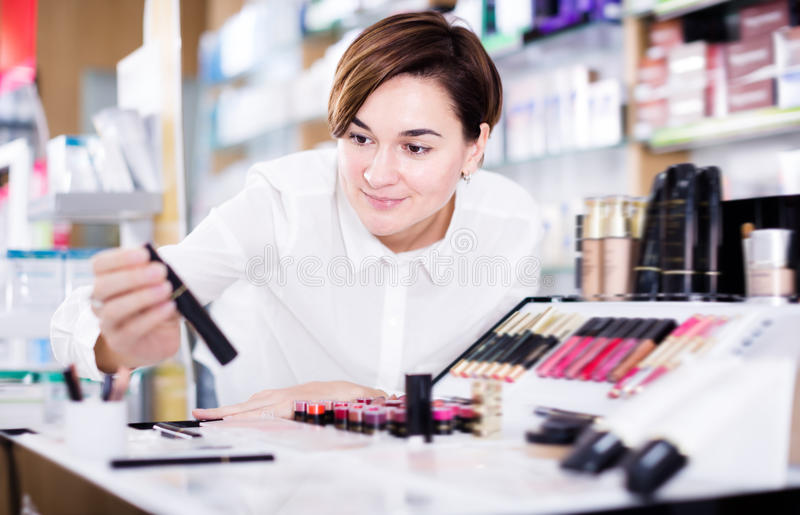 Young female customer looking for make-up items stock photography