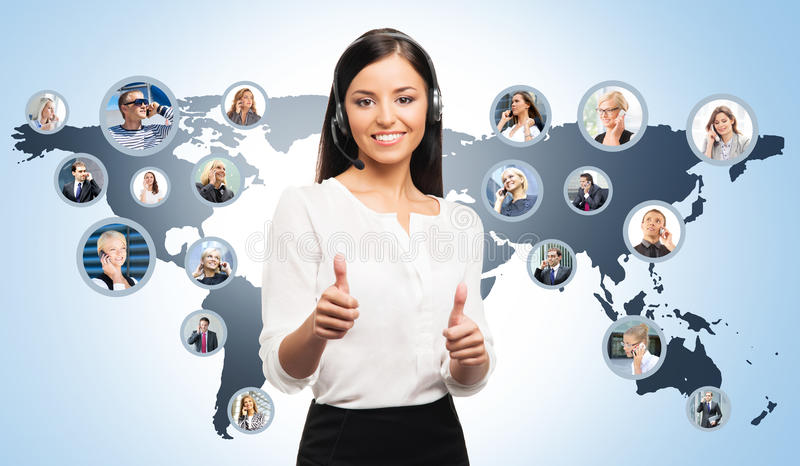 Young female customer support operator and colleagues. Young, confident and beautiful customer support operator working in a call center. World map on a stock images