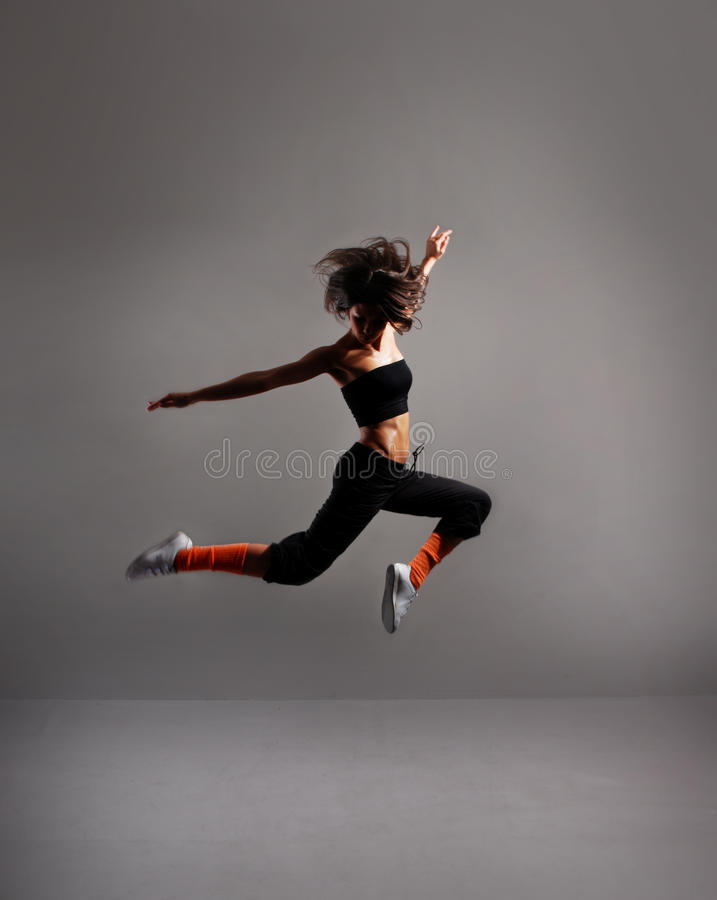 A young female dancer is performing a jump stock images