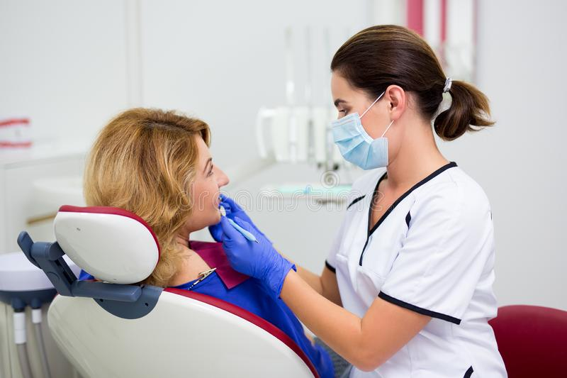 Young female dentist examining mature woman`s teeth in clinic stock photography