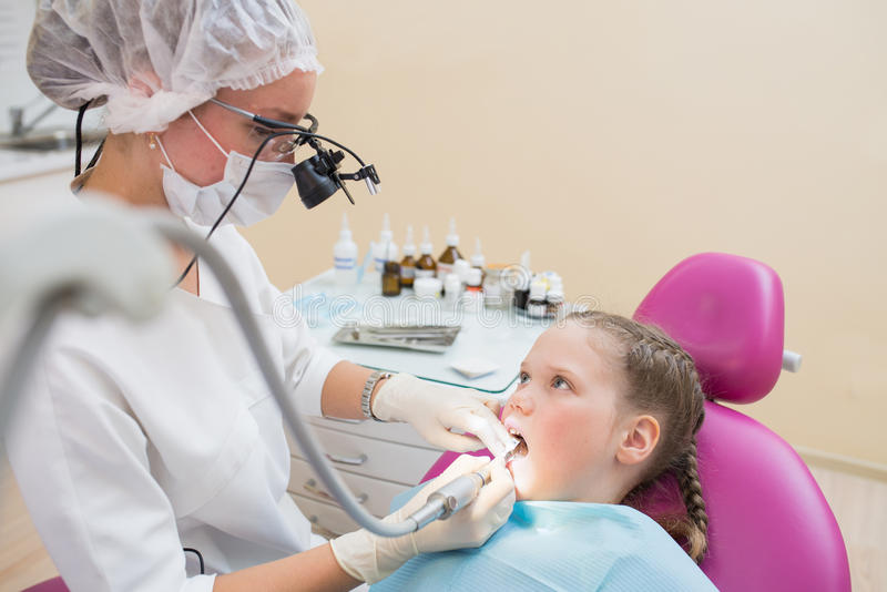 Young female dentist in loupe binoculars checked and curing teeth of child patient sitting in dental chair. Young female dentist in loupe binoculars checked and royalty free stock photos