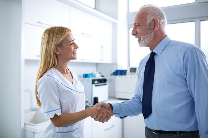Young female dentist and patient are shaking hands. In a dental office stock photo