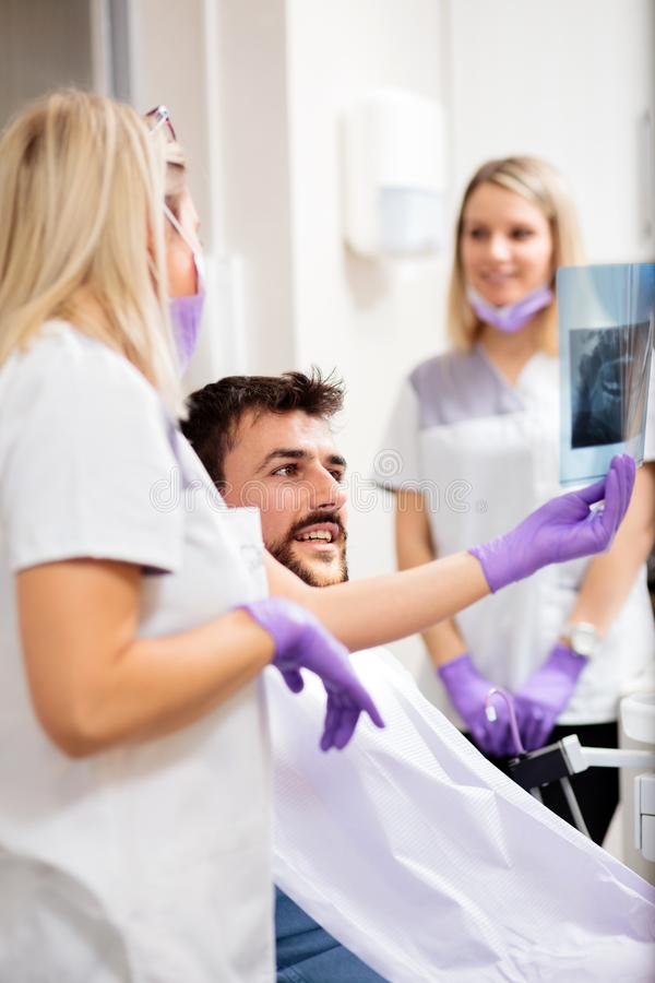 Young female dentist showing x-ray image to a male patient after a successful intervention royalty free stock images