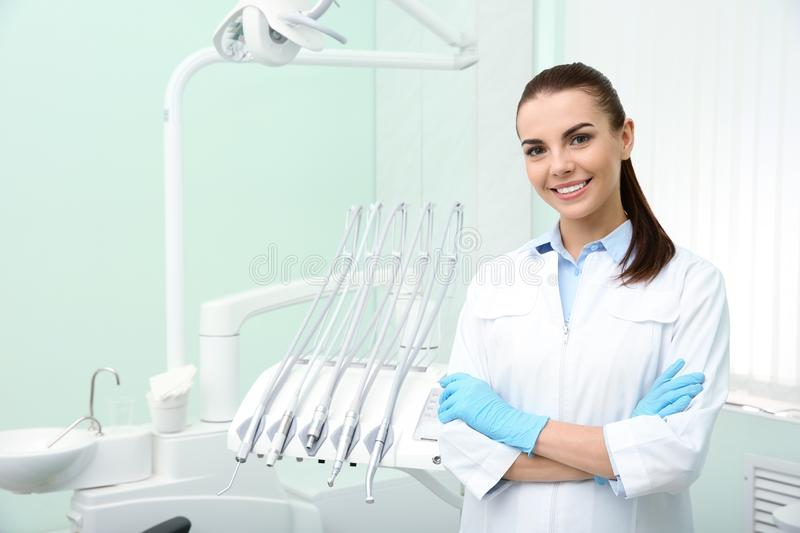 Young female dentist in white coat at workplace. Space for text royalty free stock photo