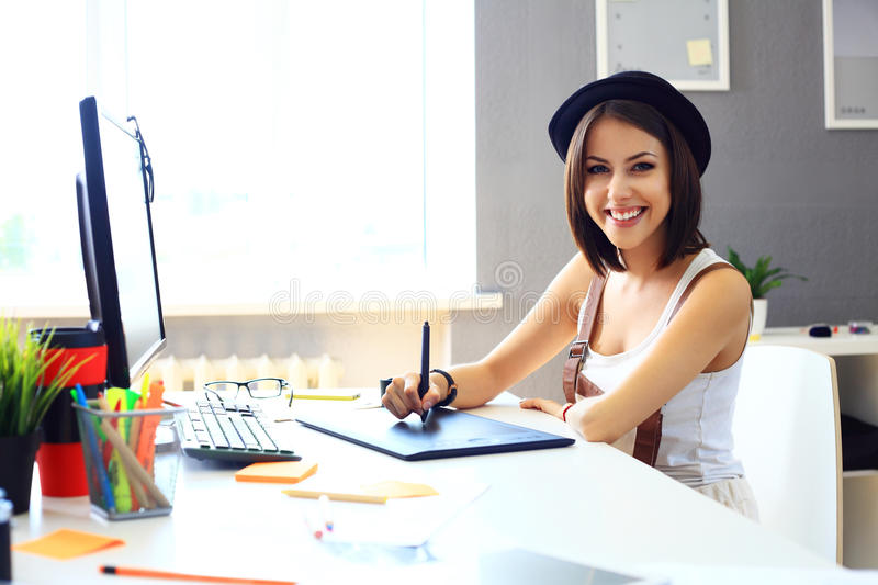 Young female designer using graphics tablet while working. With computer royalty free stock image