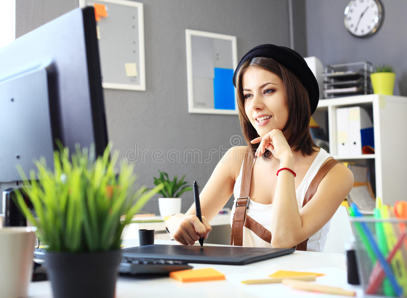 Young female designer using graphics tablet while working. With computer royalty free stock photography
