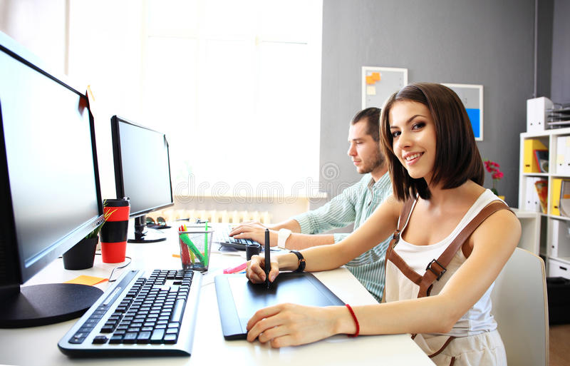 Young female designer using graphics tablet while working. With computer stock photography