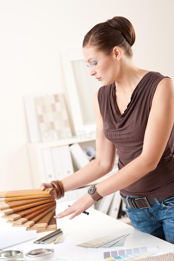Young female designer with wooden color swatches. Young female designer at office with wooden color swatches stock images