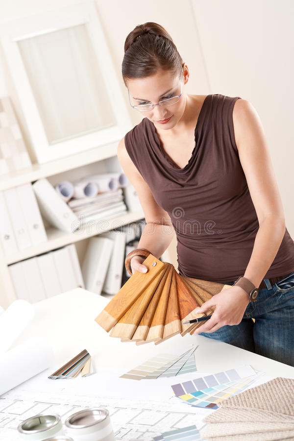 Young female designer with wooden color swatches. Young female designer at office with wooden color swatches stock photography