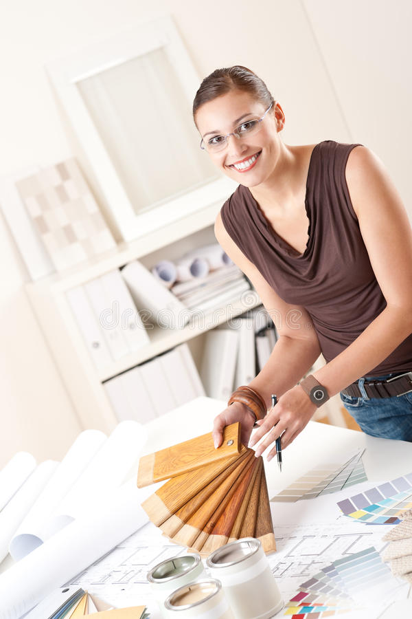 Young female designer with wooden color swatches. Young female designer at office with wooden color swatches stock image