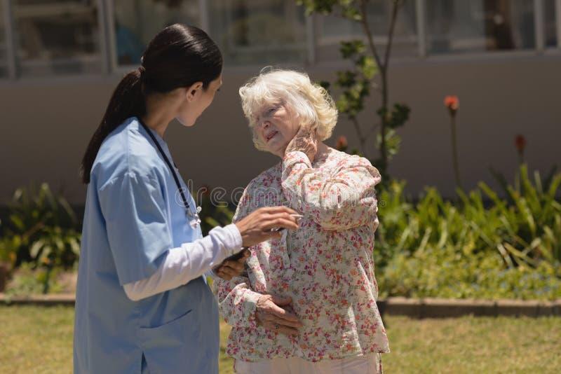 young female doctor examining senior woman in garden stock image