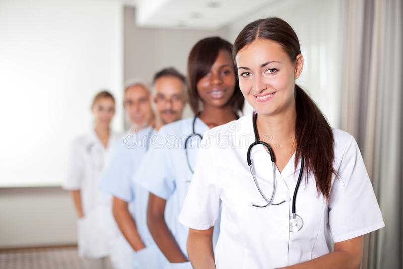 Young female doctor with group of colleagues. Mature young female doctor with group of happy successful colleagues royalty free stock photos