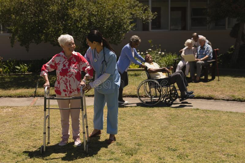 Young female doctor helping disabled senior woman in garden royalty free stock photo